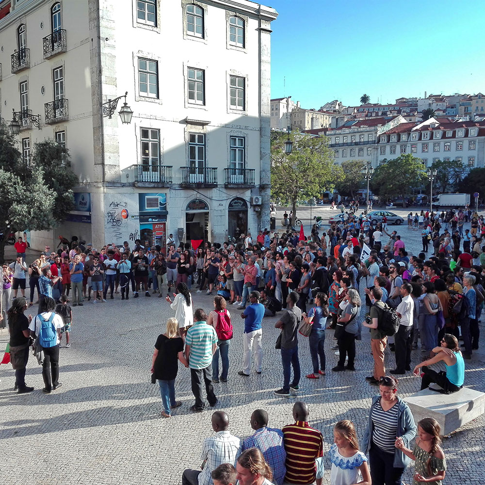 Around two hundred people gathered in a square and listening to speeches.