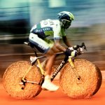 Tour de France cyclist riding a bike with tires made of circular hales of bay.