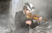 White Helmet member playing the violin amidst urban combat rubble.