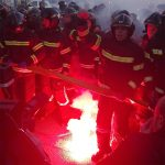 Protesting firefighters illuminated by red flare.